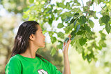 Woman in green recycling t-shirt smelling leaves at park