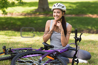 Cheerful woman wearing helmet besides bicycle in park
