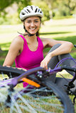 Happy woman wearing helmet with bicycle in park