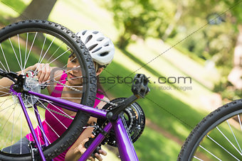 Woman trying to fix chain on mountain bike in park