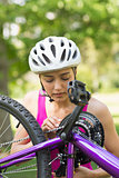 Woman in helmet trying to fix chain on mountain bike