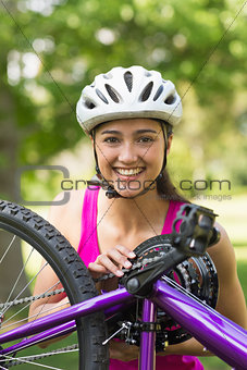 Happy young woman wearing helmet with bicycle