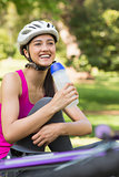 Fit woman in helmet holding water bottle at park