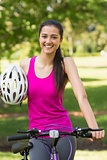 Fit woman with helmet riding bicycle at park