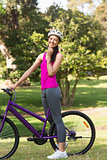 Fit woman with helmet and bicycle at park