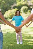 Group of friends holding hands in park