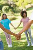 Close-up of friends holding hands in park