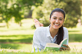 Portrait of a smiling woman reading book in park