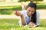 Woman eating apple while reading a book in park