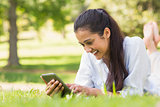 Woman text messaging while relaxing in park