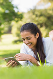 Smiling woman text messaging while relaxing in park