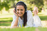 Cheerful young woman enjoying music in park