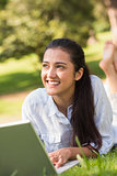 Smiling young woman using laptop in park