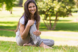 Full length portrait of smiling woman sitting in park