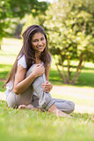 Portrait of a smiling woman sitting on grass in park