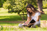 Young woman with book and pen in park