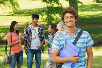 Boy with college friends in background at campus