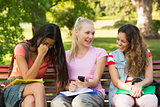 Happy female college friends sitting on campus bench