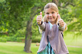 Cute young girl gesturing thumbs up at park