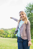 Cute smiling young girl standing at park