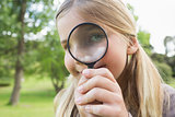 Young girl looking through magnifying glass at park