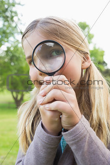 Cute young girl looking through magnifying glass at park