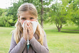Girl blowing nose with tissue paper at park