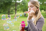 Girl blowing soap bubbles at park