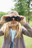 Girl looking through binoculars at park