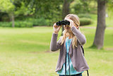Young girl looking through binoculars at park