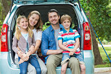 Portrait of happy family of four sitting in car trunk