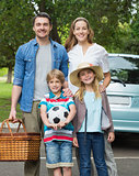 Happy family of four with picnic basket