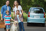 Happy family of four with car at picnic