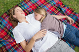 Relaxed mother and daughter lying at park
