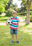 Full length portrait of a boy with ball at park