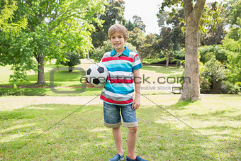 Portrait of a smiling boy with ball at park