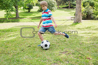 Full length of a boy kicking ball at park