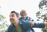 Father carrying cheerful boy on back