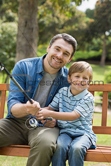Portrait of a smiling father and son fishing