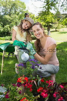 Portrait of mother with daughter watering plants