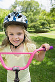 Close-up of a little girl on a bicycle at park