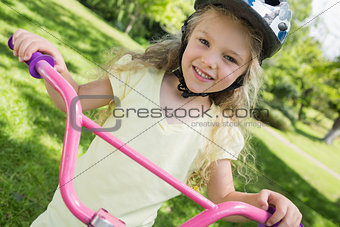 Little girl on a bicycle at summer park