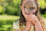 Cute girl looking through magnifying glass at park