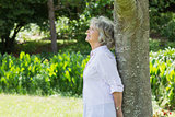 Mature woman leaning against tree trunk in park