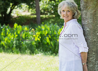 Portrait of mature woman leaning against tree trunk in park