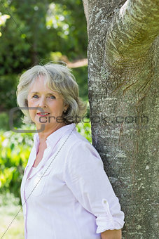 Portrait of mature woman leaning against tree trunk