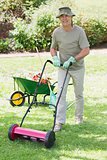 Smiling man mowing lawn