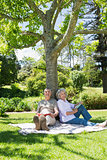 Mature couple sitting against a tree at park