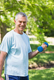 Smiling mature man exercising with dumbbell at park
