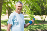 Smiling mature man with dumbbell at park